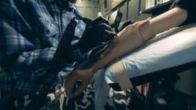 Den manliga förlagen tatuerar en man med en syntetisk hand stock video