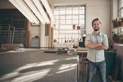 Den manliga formgivaren som ser säker med hans armar, vek i studio Fotografering för Bildbyråer