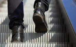Den manliga foten som går i kängor, up rulltrappan Fotografering för Bildbyråer