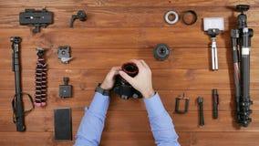 Den manliga fotografen tar en makrolins och en extra cirkel från kameran Trä bordlägga bästa beskådar Utrustning för att skjuta p arkivfilmer