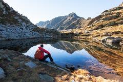 Den manliga fotvandraren tar en vila som därefter sitter en bergsjö royaltyfri fotografi