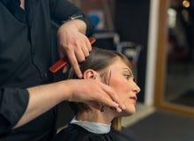 Den manliga frisören gör en frisyr till den nätta kvinnan royaltyfria foton