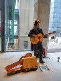 Den manliga gatakonstnären som spelar gitarren under en klimatförändringprotest, samlar som en appell till handling royaltyfria foton