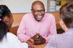 Den manliga högstadiet handleder Sitting With Students på skrivbordet i grupp arkivbild