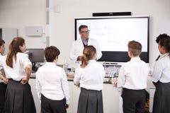 Den manliga högstadiet handleder Teaching High School studenter som bär likformig i vetenskapsgrupp arkivbilder