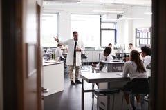 Den manliga högstadiet handleder Teaching High School studenter som bär likformig i vetenskapsgrupp royaltyfri fotografi