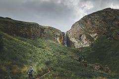 Den manliga handelsresanden klättrar berget, begrepp av att fotvandra, lopp och affärsföretag arkivbilder