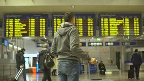 Den manliga handelsresanden som ser flyg, ankommer och information om avvikelse i flygplats lager videofilmer