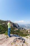 Den manliga handelsresanden som tycker om sikterna från bergen av Montserrat i Spanien och, gör ett foto Royaltyfri Fotografi
