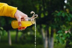 Den manliga handen h?ller hemlagad lemonad fr?n en flaska p? en bakgrund av tr?d p? naturen utomhus n?rbilden sund mat, bantar, arkivbilder