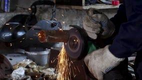 Den manliga handen klipper av stycken av vattenröret med vinkelmolar Klippa av ett stål med färgstänk av gnistor på konstruktion stock video