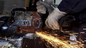 Den manliga handen klipper av stycken av vattenröret med vinkelmolar Klippa av ett stål med färgstänk av gnistor på konstruktion lager videofilmer