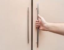Den manliga handen är öppen skåpdörrarna, ljust trä Fotografering för Bildbyråer