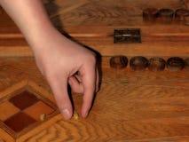 Den manliga handen rymmer tärning i leken av brädspel royaltyfria foton