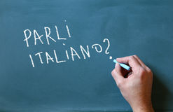 Den manliga handen som skriver över den svart tavlan, talar du italienare royaltyfri fotografi