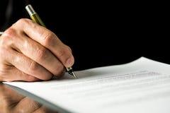 Den manliga handen som undertecknar ett avtal, anställning skyler över brister, det lagliga dokumentet Arkivfoto