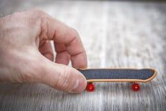 Den manliga handen startar leksakskateboarden Startande affärsidé Startup ungt företagsbegrepp Abstrakt begrepp börjar begrepp Arkivbild
