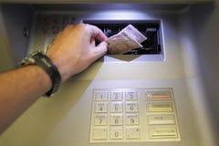 Den manliga handen tar europengar från en bankomat Pengarbetalning, finanstransaktion och ekonomibegrepp royaltyfri bild