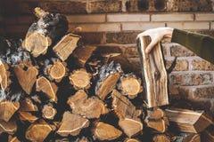 Den manliga handen tar stycket av trä från högen staplat vedträ Royaltyfria Bilder