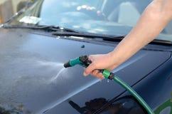 Den manliga handen tvättar bilen med en slang Arkivfoto