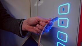 Den manliga handproppen och kopplar från USB kabel till den fria laddande porten arkivfilmer