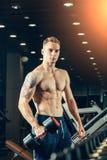 Den manliga idrottsman nen med en hantel i idrottshallen lutar på Royaltyfria Foton