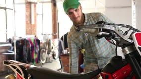 Den manliga idrottsmannen fyller hans enduromotorcykel med bensin lager videofilmer