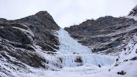 Den manliga isklättraren står på headwallen av en lång och brant vattenfall i fjällängarna fotografering för bildbyråer