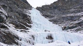 Den manliga isklättraren står på headwallen av en lång och brant vattenfall i fjällängarna arkivfoton