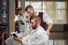 Den manliga klienten som visar frisyr i telefon i barberare, shoppar royaltyfri foto