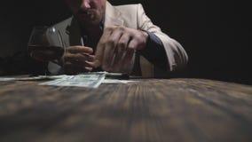 Den manliga knarkaren som gör linjen av kokain med kreditkorten och sniffar drogen rullade igenom, av sedel från telefonskärmen d stock video
