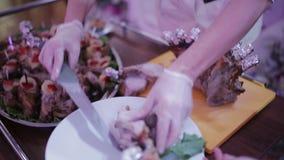 Den manliga kocken i restaurangkorridor klippte upp stekgåsen framme av entusiastiska gäster lager videofilmer