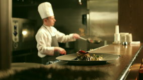 Den manliga kocken lagar mat Flambe i restaurangkök arkivfilmer