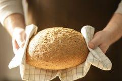 Den manliga kocken med släntrar av bröd arkivfoto