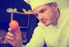 Den manliga kocken som avgör på bästa frukter shoppar in Royaltyfria Foton