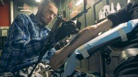 Den manliga konstnären tatuerar en syntetisk hand och torkar den stock video