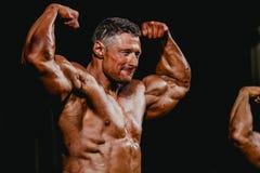 Den manliga kroppsbyggaren som segrar konkurrens, poserar Arkivbilder