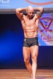 Den manliga kroppsbyggaren visar hans bästa på mästerskapet på etapp Arkivbilder