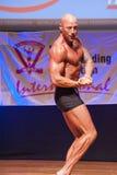 Den manliga kroppsbyggaren visar hans bästa på mästerskapet på etapp Arkivbild