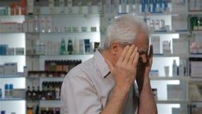 Den manliga kunden kommer till apoteket med huvudvärk stock video