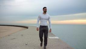 Den manliga löparen promenerar den härliga kusten, medan lyssna till musiken med hörlurar ready till genomköraren stock video