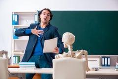 Den manliga l?raren och den skelett- studenten i klassrumet royaltyfri foto