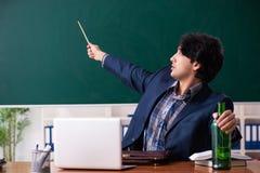 Den manliga l?raren som dricker i klassrumet arkivfoto