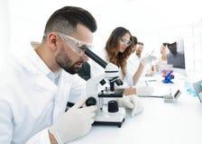 Den manliga labbteknikeren ser prövkopian under ett mikroskop Royaltyfri Bild