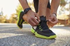 Den manliga löparen som squatting i vägen som binder hans sportar, skor tätt upp Arkivbild