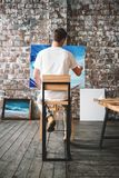 Den manliga målaren sitter på främst kanfas för stol och teckningsbild i studio Konstgrupp och seminarium Konstnärmålningprocess  royaltyfri foto