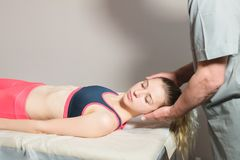 Den manliga manuella inv?rtes terapeutmass?ren behandlar en ung kvinnlig patient V?rm skuldrorna och halsen upp royaltyfri bild