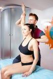 Den manliga massageterapeuten i ett medicinskt rum gör en flicka som ligger på en massage för att bordlägga massagen för muskelsi