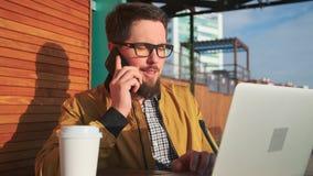 Den manliga medborgaren talar av mobiltelefonen som sitter på terrassen som skriver på bärbara datorn stock video