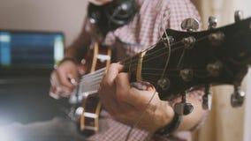 Den manliga musikern spelar gitarren, räcker tätt upp, fokusen på gitarrfretboarden Arkivbilder